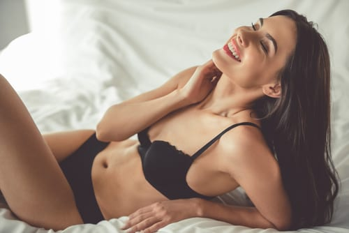 beautiful young woman in black lingerie is smiling while lying on bed-img-blog